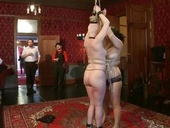 On the Upper Floor, cuties all over the place are being punished. There`s two secured up face to face getting caned, two more being flogged while holding a stripper pole, two more getting spanked by a man and her face slapped by a woman, two more getting